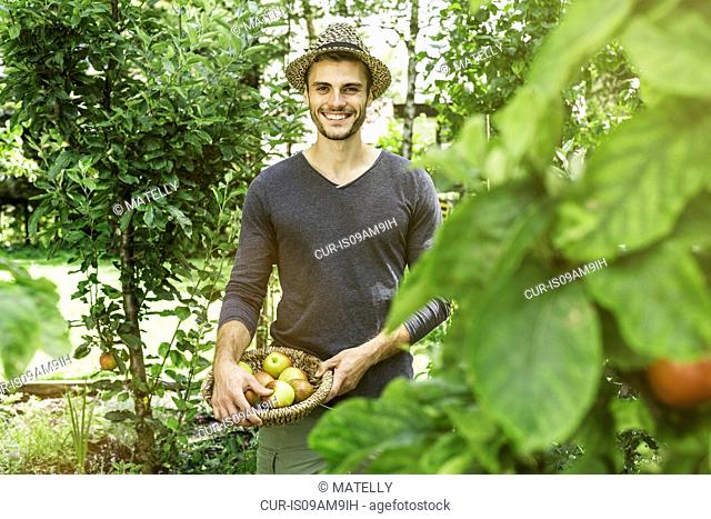 Man in garden holding bowl of apples