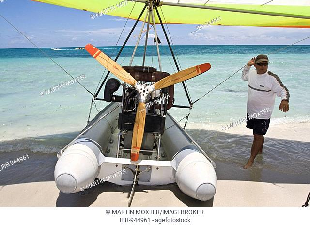 Pilot of a motorised hang glider waiting for passengers on a beach, UL-Trike, Ultra Light airplane with a life boat, Varadero, Cuba, Caribbean, Central America