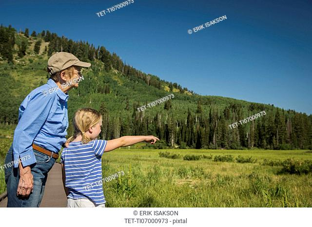 USA, Utah, Lake City, Girl (4-5) with grandmother standing on boardwalk by wetland