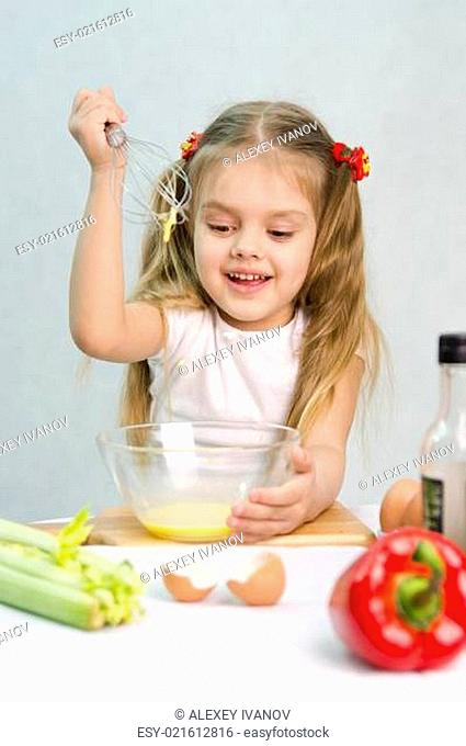Girl playing cook churn whisk eggs in a glass bowl