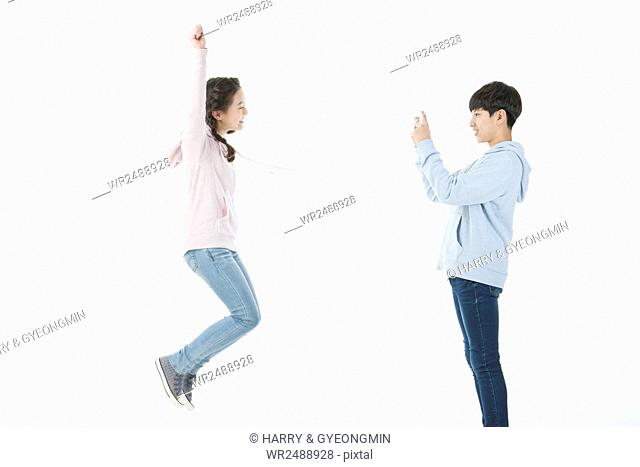Side view of smiling school boy and school girl in casual clothes jumping and taking picture with smartphone