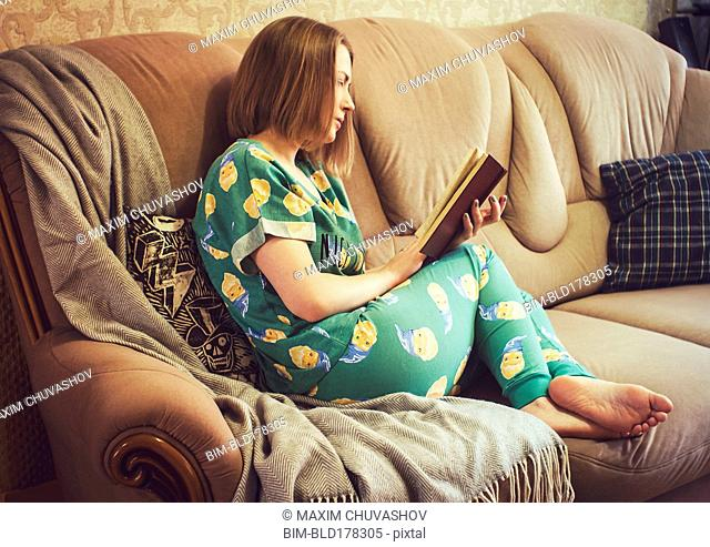 Caucasian woman reading book on sofa