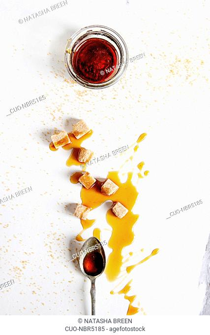Homemade liquid transparent brown sugar caramel in glass jar with spoon and cane sugar cubes over white marble background. Flat lay, space