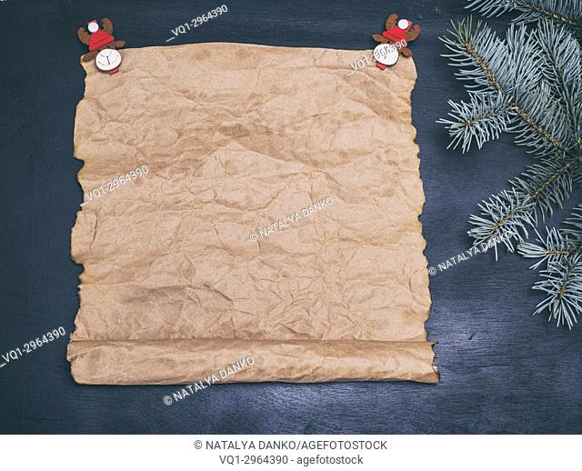 Empty scroll of brown kraft paper on black background and New Year decor