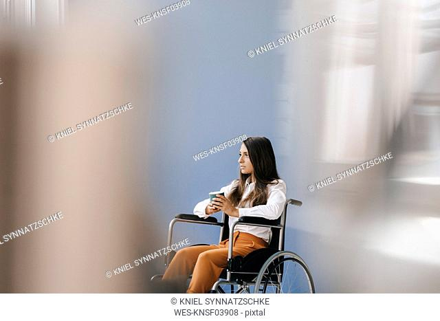 Young handicapped woman sitting in wheelchair, looking worried