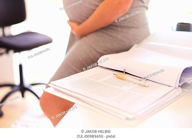 Mid section of pregnant young woman leaning against desk
