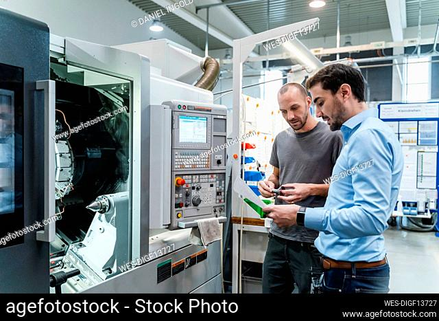 Businessman discussing over document with maintenance engineer while standing at industry