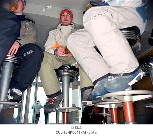 3 snowboarders sitting in a bar
