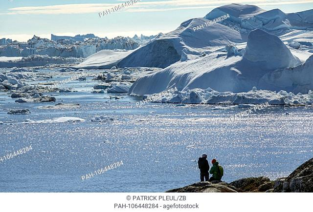 22.06.2018, Gronland, Denmark: Two tourists standing on the shore in front of large icebergs in the sea near the coastal town of Ilulissat in western Greenland