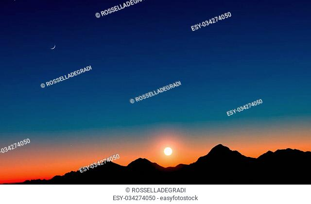 Sunset with mountains in silhouette with the moon
