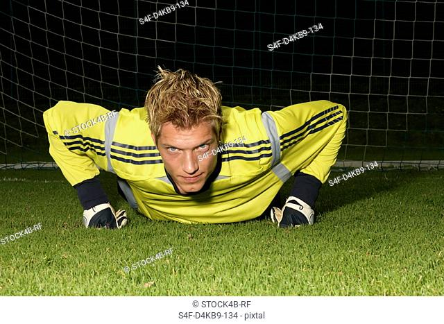 Young goalkeeper with blond hair doing push-up