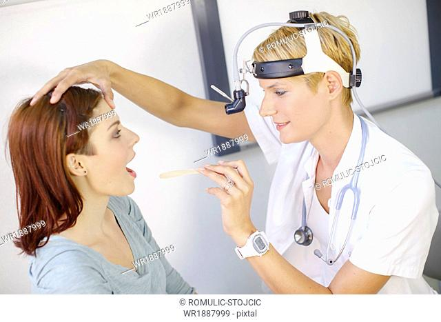 ENT physician Examines the Throat of a Female Patient