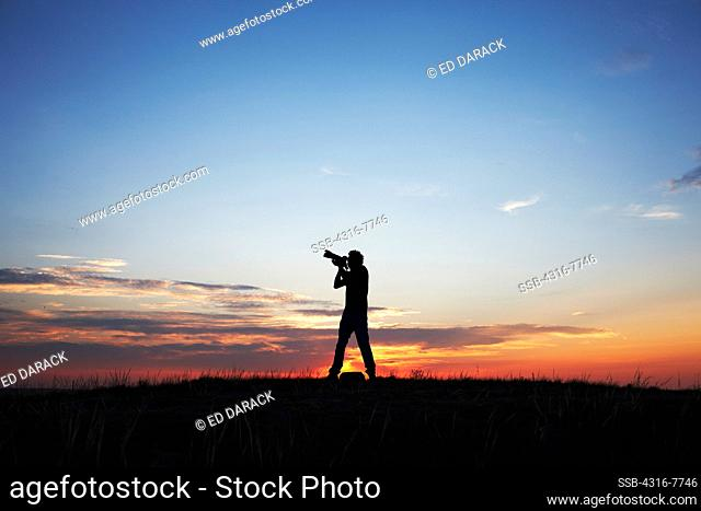 Silhouette of man aiming camera with telephoto zoom lens into sky at dawn