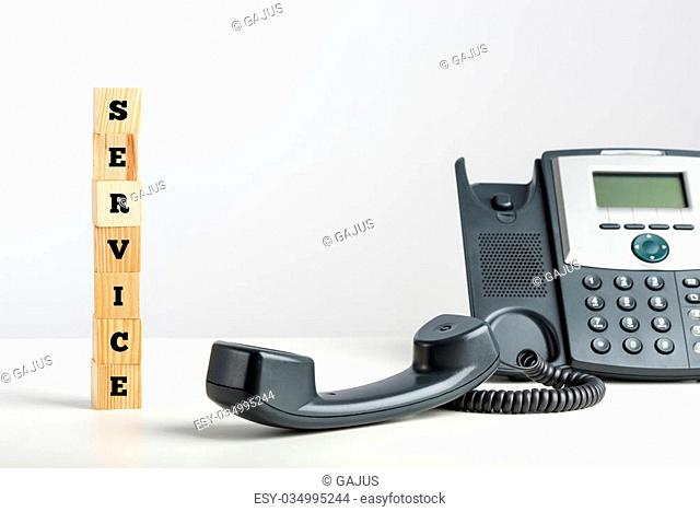 Service concept with the word Service written on stacked wooden cubes alongside a telephone with the handset off the hook in a communication, support