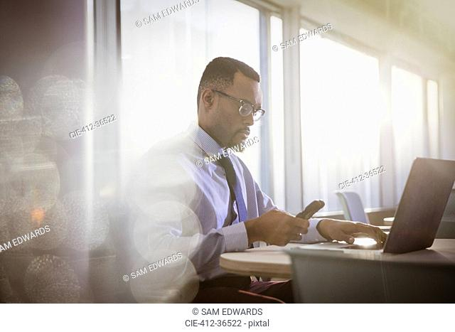 Serious businessman texting with cell phone at laptop in office