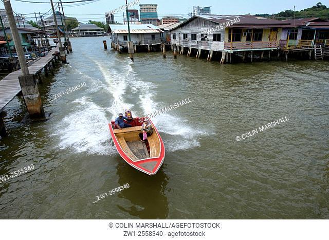 Speedboat water taxi passing walkway and shacks on stilts in Brunei River, Water Village (Kampong Ayer), Bandar Seri Begawan, Brunei