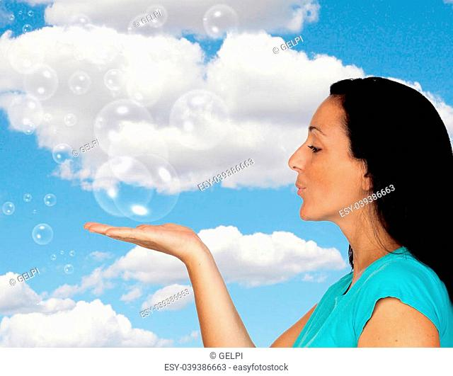 Adorable woman blowing bubbles with a blue sky of background