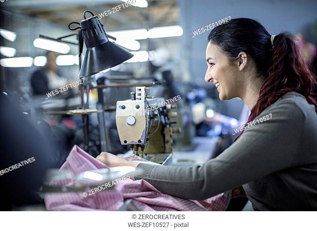 Seamstress in factory sewing clothes