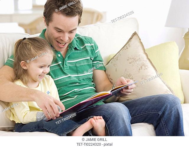 Father reading to daughter on sofa