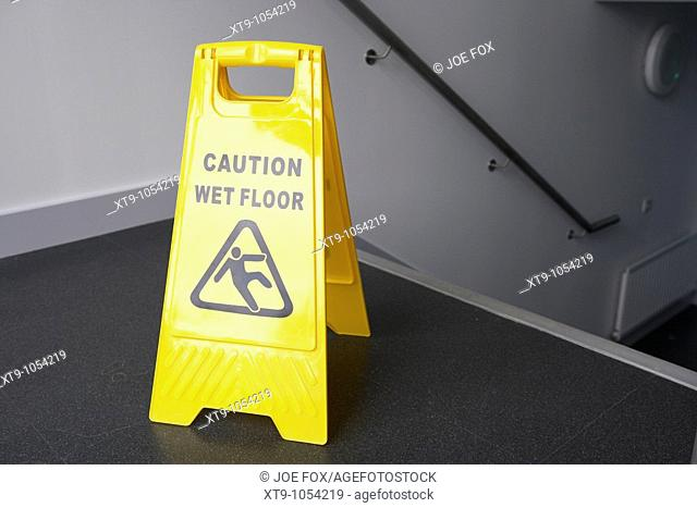 caution wet floor sign at the top of a set of stairs in a modern building