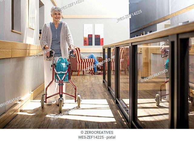 Senior woman in retirement home pushing wheeled walker