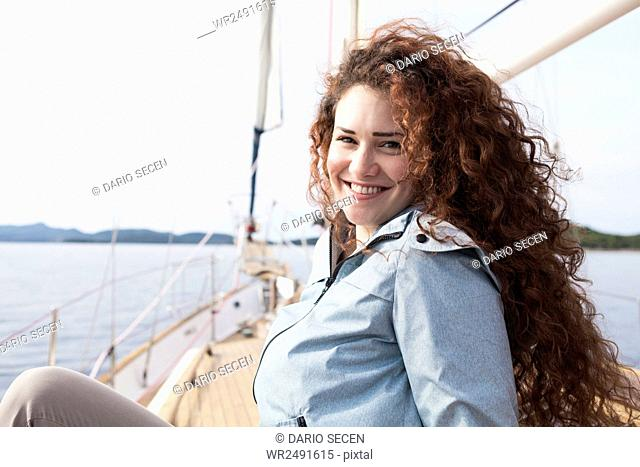 Portrait of happy young woman on yacht