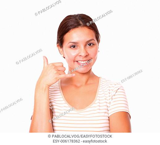 Portrait of cheerful hispanic girl with call gesture smiling and looking at you on isolated white background