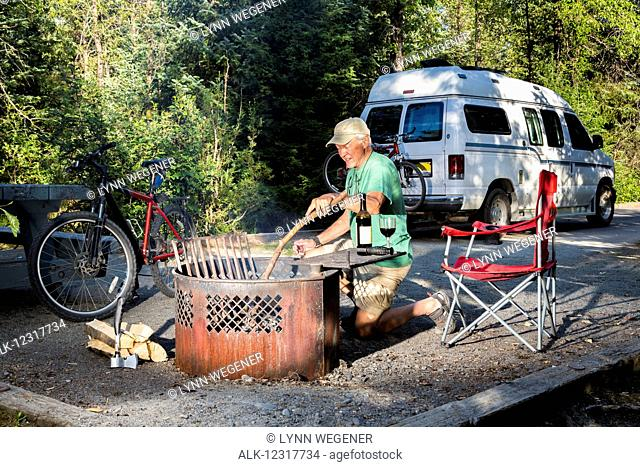 Male camper enjoying a fire in Williwaw USFS Campground with a bicycle and Sportsmobile camper van in the background in Portage Valley, Summer, Alaska, USA