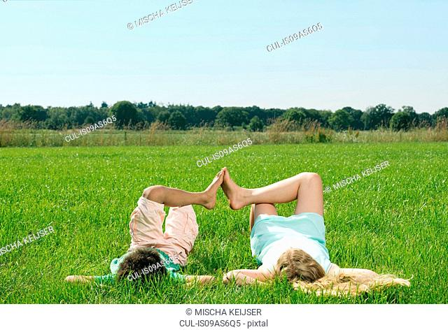Rear view of girl and boy with feet touching lying in field