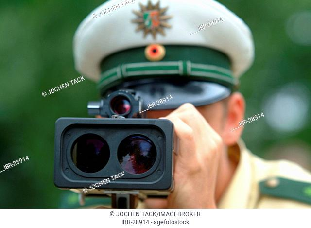 DEU, Germany, Essen: Traffic speed control in a speeding zone of 30 km/h near a school, with a laser measure gun. Daily police life