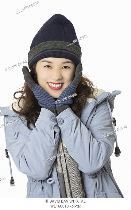 Beautiful Asian woman wearing winter clothes isolated on a white background