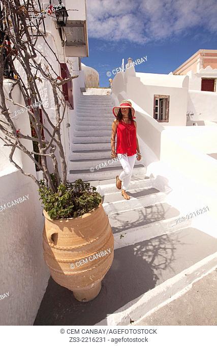 Tourist woman walking down the stairs, Oia, Santorini, Cycldes Islands, Greek Islands, Greece, Europe