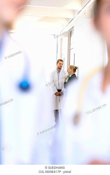 Over shoulder view of male doctor and woman having discussion in hospital corridor