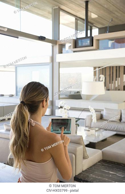 Woman with digital tablet setting digital security system in modern, luxury home showcase interior living room