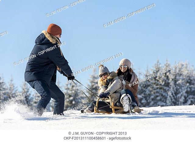 Young man pulling girls on winter sledge snow countryside