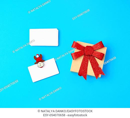 empty white paper business cards and holiday clothespins on a blue background, brown box with a red bow, top view