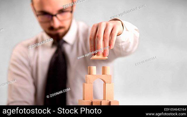 Young handsome businessman using wooden building blocks