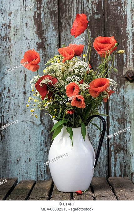 floral still life, wild flowers and poppy blossoms in old enamel pot in front of an old door