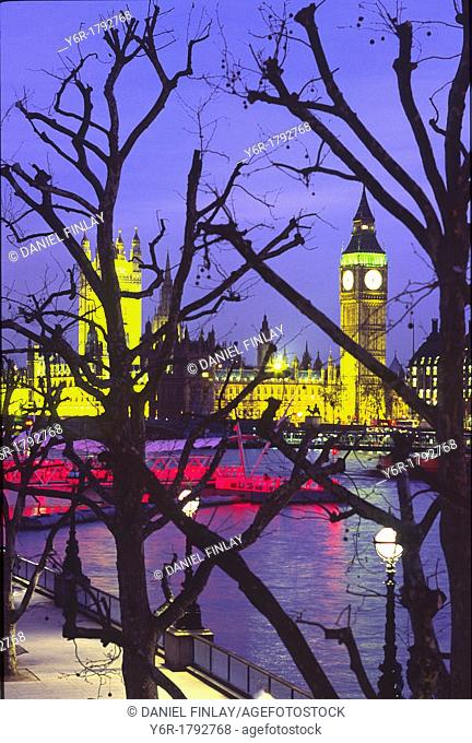 View of an illuminated Big Ben and the Houses of Parliament across the River Thames at nightfall as seen from Hungerford Footbridge in London, England
