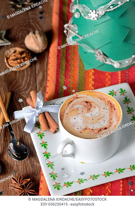Cup of coffee and Christmas decorations on wooden table
