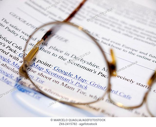 Reading glasses on magazine article. Esplugues de Llobregat city. Barcelona Metropolitan Area, Catalonia, Spain