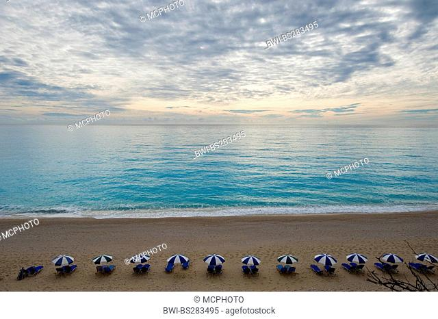 view at the sea over a sand beach with canvas chairs and sunshades, Greece, Lefkada
