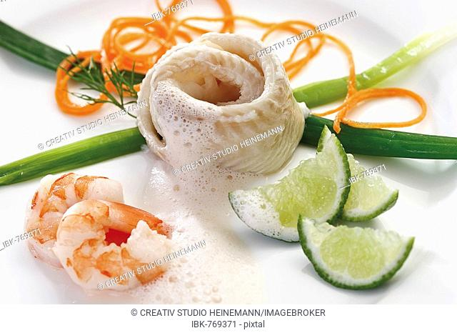 Seafood dish: rolled halibut wrapped in a leek bow with leeks, lime wedges, finely sliced carrots, shrimp (prawns) and frothy white wine sauce