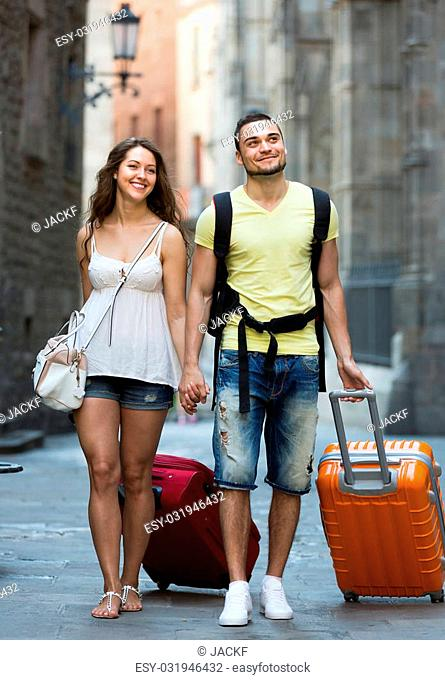 Positive smiling couple of travelers with baggage heading to hotel on foot