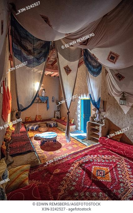 Interior living space with hung fabrics through out in traditional mud-built brick house in Tighmert Oasis, Morocco
