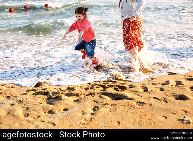 Young loving mother with smiling daughter running towards her on sunny beach, happy mom hug little girl, enjoying spending time together on summer seaside