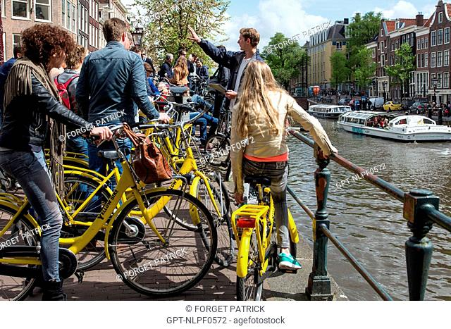 GROUP OF TOURISTS ON YELLOW BIKES WITH A TOUR GUIDE, PRINCENGRACHT, AMSTERDAM, HOLLAND