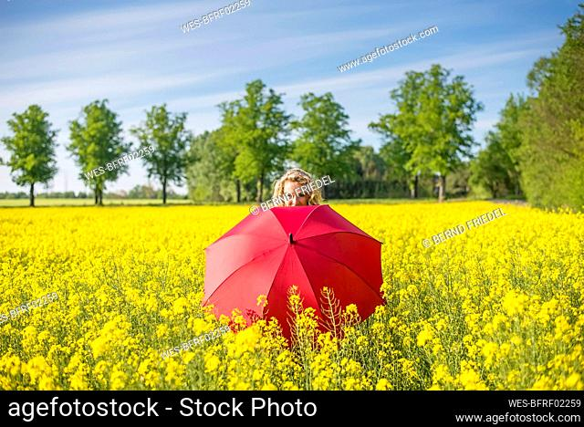 Mature woman with red umbrella standing amidst oilseed rapes against sky