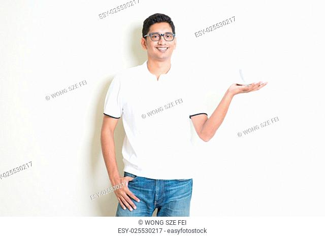 Indian guy holding a cup of coffee on hand. Asian man standing on plain background with shadow and copy space. Handsome male model