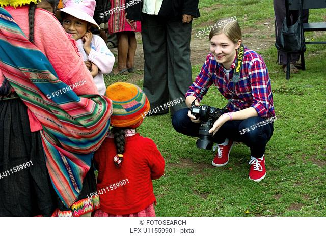 Tourist taking picture of Quechua Indian people, Chumpepoke Primary School, Poques, Sacred Valley, Cusco Region, Peru